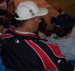 "Wayne ""Kriv-dog"" Krivsky talking on a cell phone while wearing a hat with logos for the Arizona Diamonbacks, the Minnesota Twins, the Chicago Cubs, and the Cincinnati Reds"