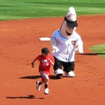 A kid flying by the Goodyear mascot during a between-innings contest