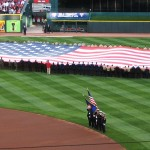 Service members unfurled a giant flag in the outfield