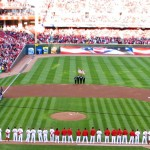 Reds and Brewers players line up on the foul line for the National Anthem