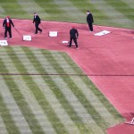 The tuxedo-wearing grounds crew refreshes the field during the 7th inning stretch