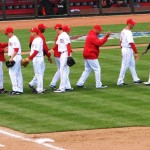 The Reds high-five each other in the middle of the field after winning the first game of 2012.