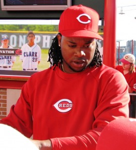 Johnny Cueto hands a fan's hat back after signing it