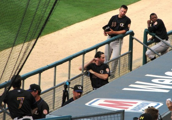 Paul Janish and other members of the Louisville Bats relax during an Indians' pitching change.