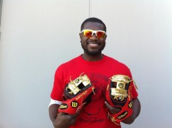 Brandon Phillips holding 2 gold-colored baseball gloves