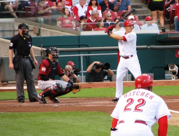 Chris Heisey bats while first base coach Billy Hatcher watches.