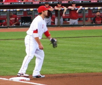Joey Votto stands with his foot on the bag to field a throw to first base.