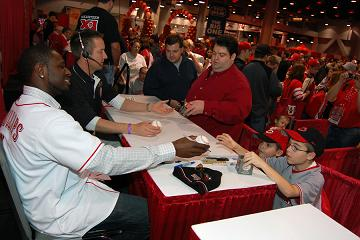 Brandon Phillips signs a baseball for a young fan at Kahn\'s Redsfest XI. Credit: The Cincinnati Reds