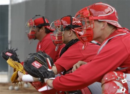 Cincinnati Reds catchers Corky Miller, left, Devin Mesoraco, center, and Chris Denove catch during a bullpen session during baseball spring training Sunday, Feb. 20, 2011, in Goodyear, Ariz. (AP Photo/Mark Duncan)
