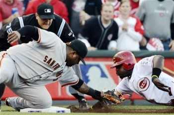 Brandon Phillips is out trying to snag third on a passed ball. (AP Photo/Michael Keating)