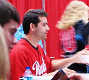 Votto handing a kid his autographed item.
